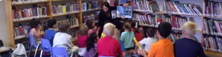 Woman reading to a group of children in the library.